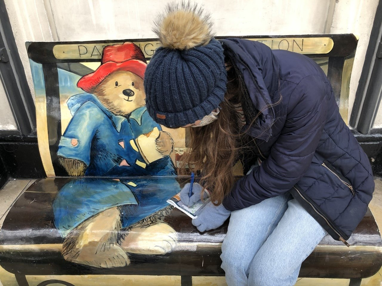 Woman completing a treasure trail map on a paddington bear bench in London