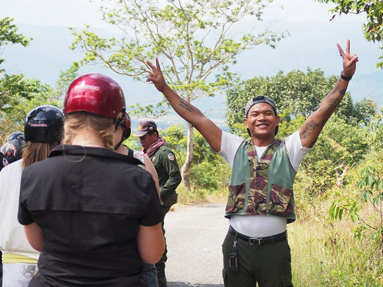 Guide smiling and raising his arms with peace signs