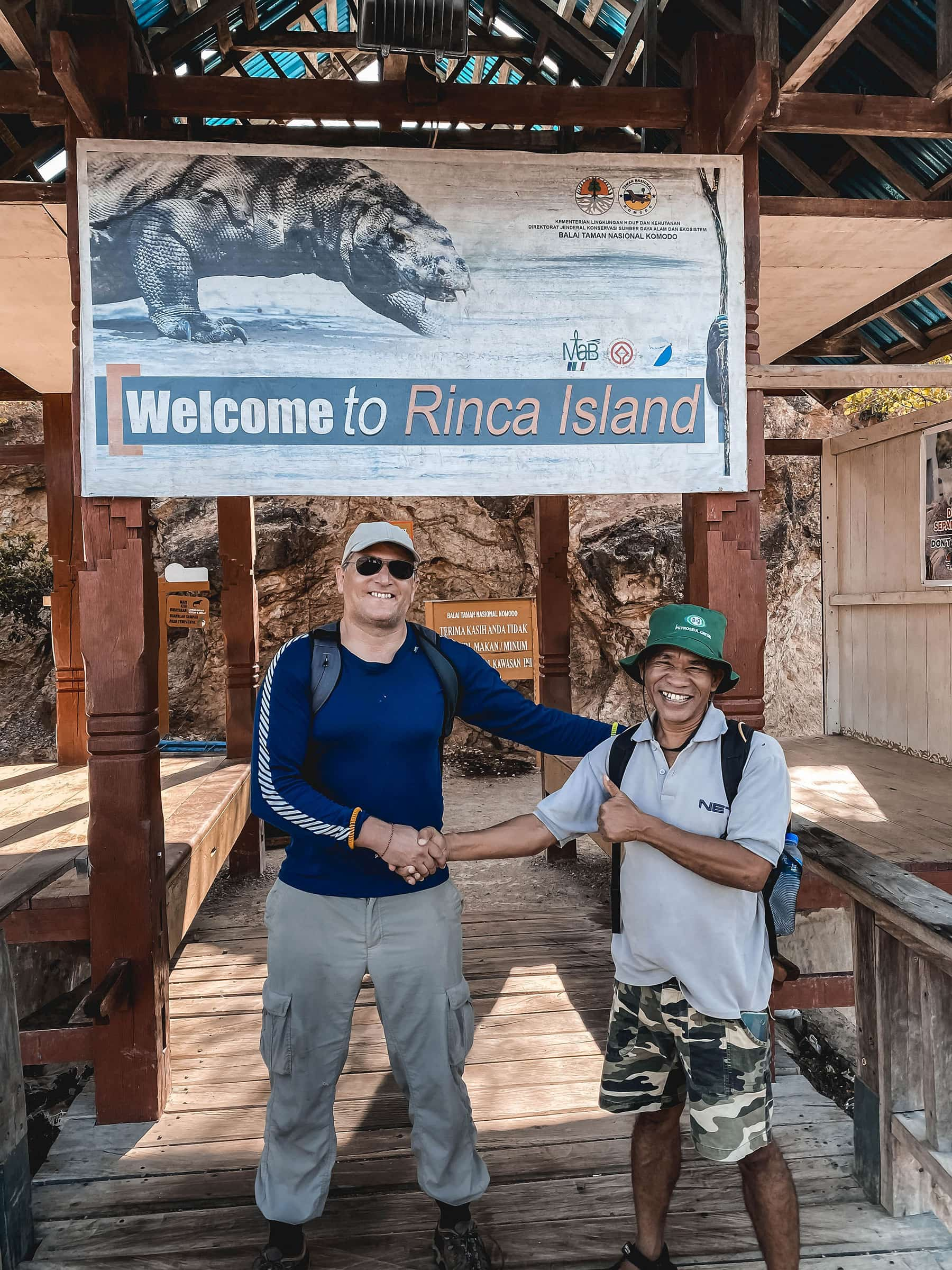 Traveller shaking hands with a guide on wooden walkway under a sign for rinca island